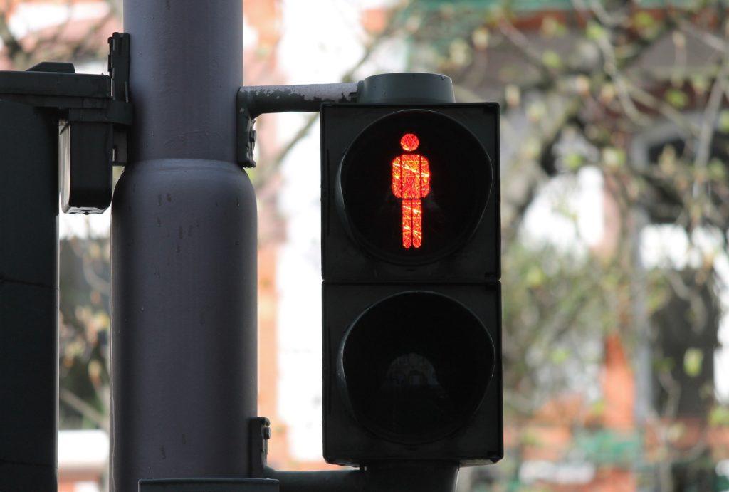 Fußgänger müssen an einer roten Ampel warten, sonst drohen Bußgelder.